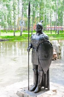 Rzeźba czarnego rycerza z żeliwną tarczą i włócznią osadzoną na naturze