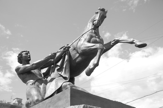 Rzeźba poskramiaczy koni (1851) autorstwa petera klodta na moście anichkov w sankt-petersburgu w rosji. czarny i biały