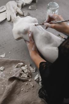 Rzeźbiarz maluje statuetkę pędzlem