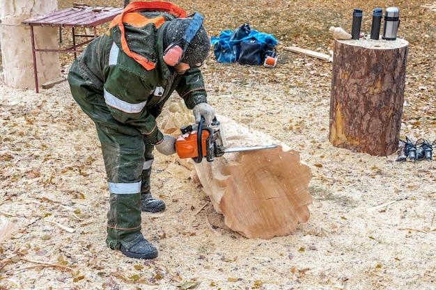 Rzeźbiarz wycina piłą łańcuchową oryginalną drewnianą figurę z dużej kłody