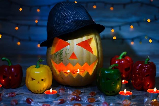 Rzeźbiona dynia w kapeluszu otoczona rzeźbioną papryką zapala cukierki i świeczki