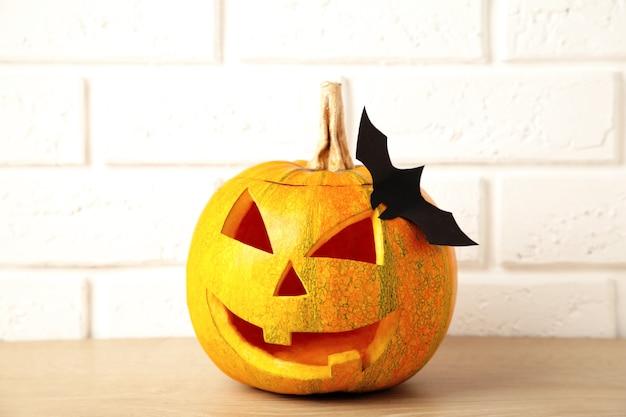 Rzeźbiona świecąca dynia i czarny nietoperz na jasnym tle. święto halloween. widok z góry