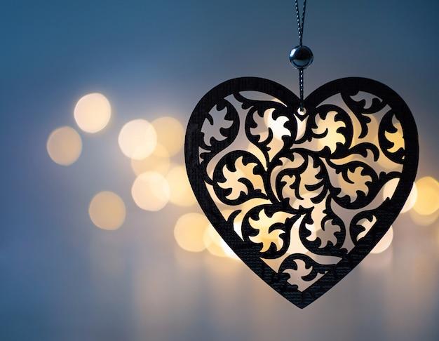 Rzeźbione drewniane serce wiszące na ciemnoniebieskim tle ze złotym bokeh.