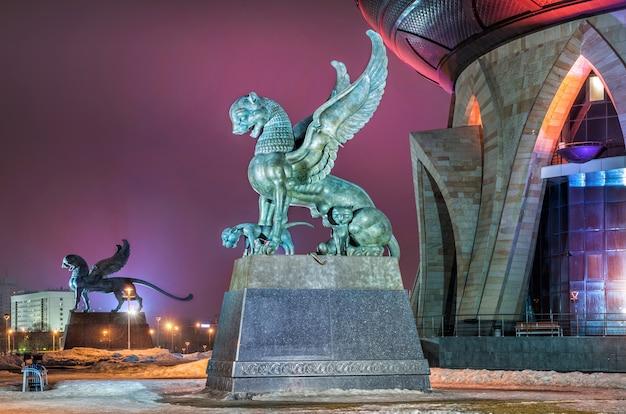 Rzeźby rodziny skrzydlatych lampartów z młodymi na tle liliowego nocnego nieba w pobliżu centrum rodziny w mieście kazań