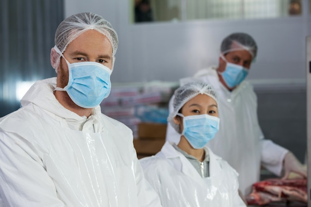 Rzeźnicy w ochronnej odzieży roboczej w fabryce mięsnej