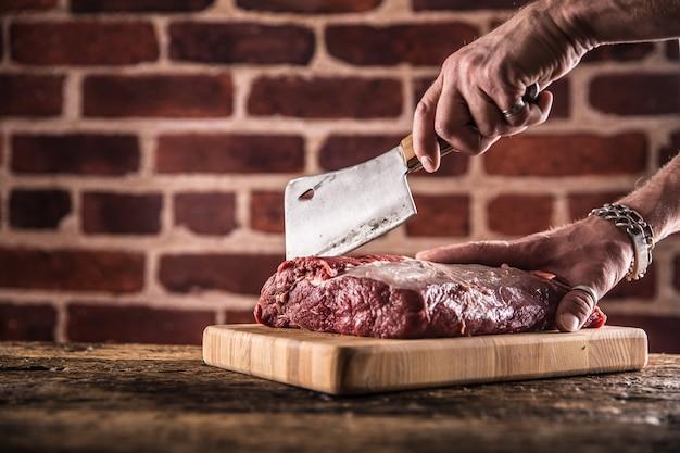 Rzeźnik człowiek ręce cięcia surowego stek wołowy w rzeźni.