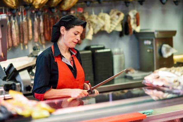 Rzeźnik ostrzący nóż w sklepie mięsnym