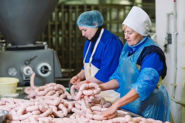 Rzeźnik przetwarzający kiełbasy w fabryce mięsnej.