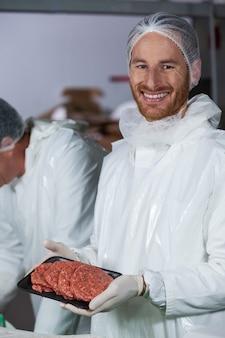 Rzeźnik trzyma surowe mięso paszteciki ułożone w zasobniku