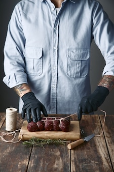 Rzeźnik wiąże mięso sznurem do wędzenia, na stole z gatunkami