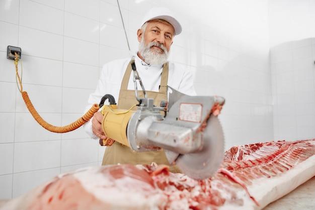 Rzeźnik za pomocą noża elektrycznego do cięcia wieprzowiny w fabryce.