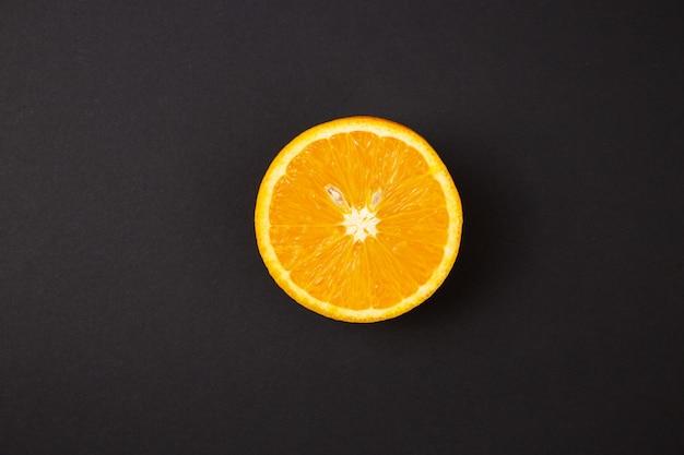 Rżnięta pomarańcze na abstrakcjonistycznym czarnym tle