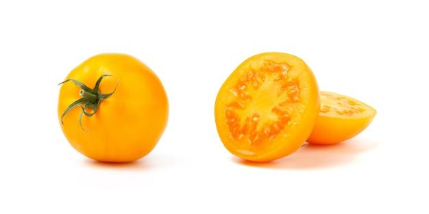 Rżnięty i cały żółty pomidor odizolowywający na białym tle