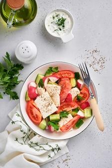 Rzodkiew, ogórek, pomidor, papryka i ser feta z przyprawami pieprz i oliwa z oliwek w białej misce na szarym tle łupkowym, kamiennym lub betonowym. koncepcja zdrowej żywności. widok z góry.