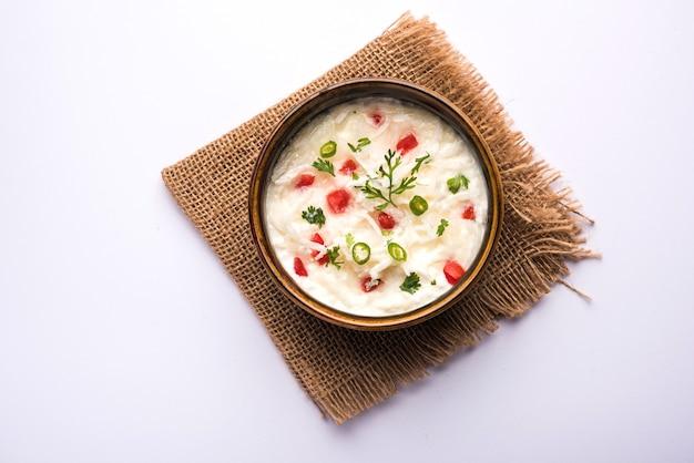 Rzodkiew raita lub daikon lub mooli koshimbir podawane w misce na nastrojowym tle. selektywne skupienie. indyjska zdrowa żywność