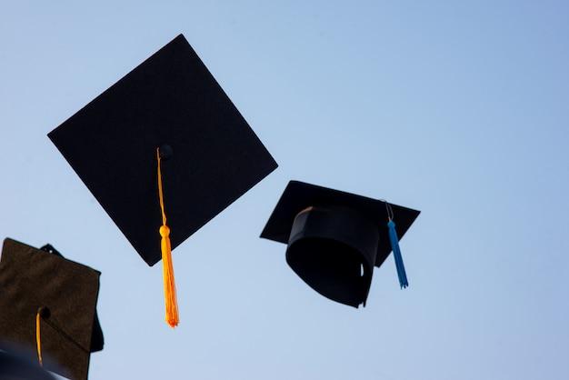 Rzuć czarny kapelusz absolwentów na niebie.
