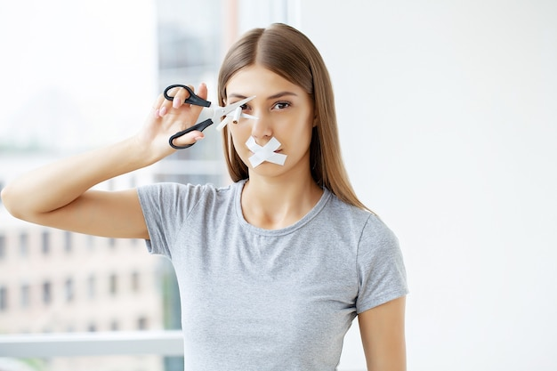 Rzuć palenie, kobieta z zamkniętymi ustami przecina papierosa nożyczkami.