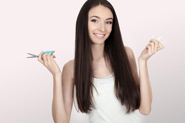 Rzuć palenie koncepcja. młoda kobieta cięcia papierosów nożyczkami szczęśliwy uśmiechnięty. skoncentruj się na dłoni, nożyczkach i papierosach