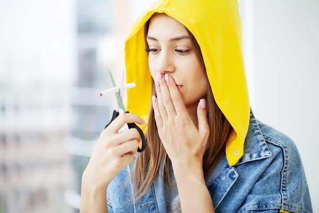 Rzuć palenie, młoda kobieta łamie papierosa, zachęcając do rzucenia palenia