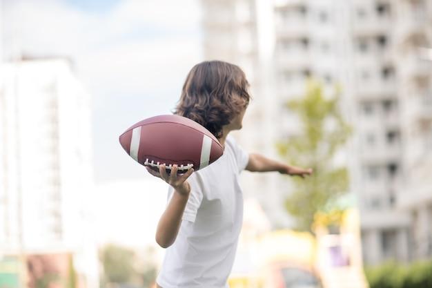 Rzucanie piłki. chłopiec w białej koszulce rzuca piłką