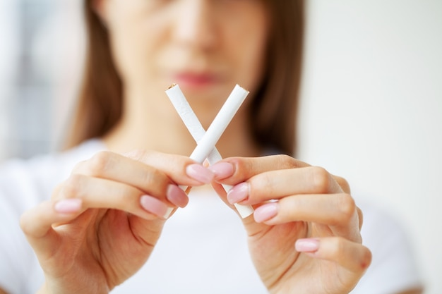 Rzucić palenie, młoda dziewczyna trzymając w rękach papierosy.