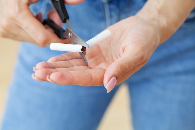 Rzucić palenie, młoda dziewczyna trzymając w rękach złamanego papierosa.