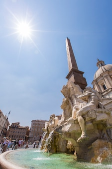 Rzym, włochy - 16 lipca 2013: niezidentyfikowani ludzie przez fontana dei quattro fiumi, piazza navona w rzymie. piazza navona to popularne miejsce w rzymie, trzecie najczęściej odwiedzane miasto w unii europejskiej.