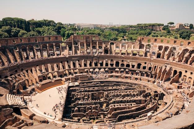 Rzym, włochy - 20 czerwca 2018: panoramiczny widok wnętrza koloseum w rzymie. letni dzień z błękitnym i szarym niebem