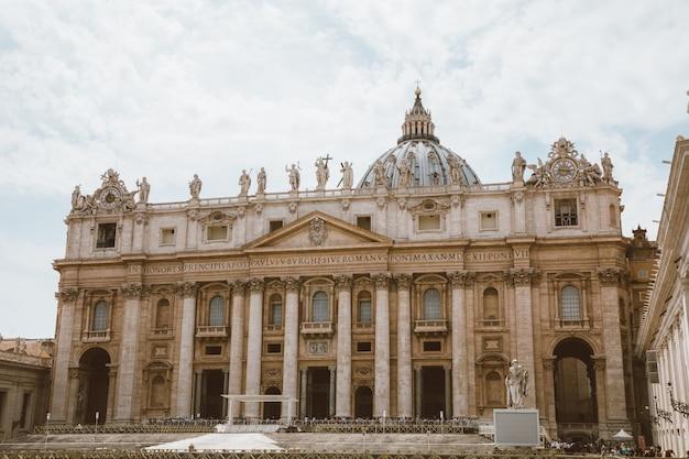 Rzym, włochy - 22 czerwca 2018: panoramiczny widok na papieską bazylikę świętego piotra (bazylika świętego piotra) w watykanie i plac świętego piotra. letni dzień i ludzie chodzą