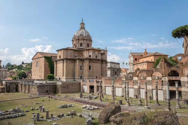 Rzym, włochy - 23 czerwca 2018: panoramiczny widok forum cezara znany również jako forum iulium, curia julia (dom senatu) i kościół santi luca e martina