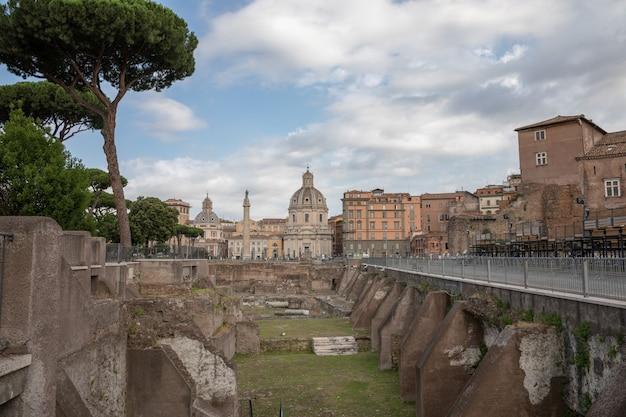 Rzym, włochy - 23 czerwca 2018: panoramiczny widok na forum trajana i kolumnę w rzymie, daleko kościół najświętszego imienia maryi. letni dzień i błękitne niebo