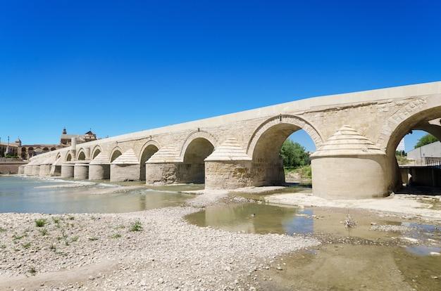 Rzymianina most i guadalquivir rzeka nad błękitnym jaskrawym niebem w cordobie, andalusia, hiszpania.