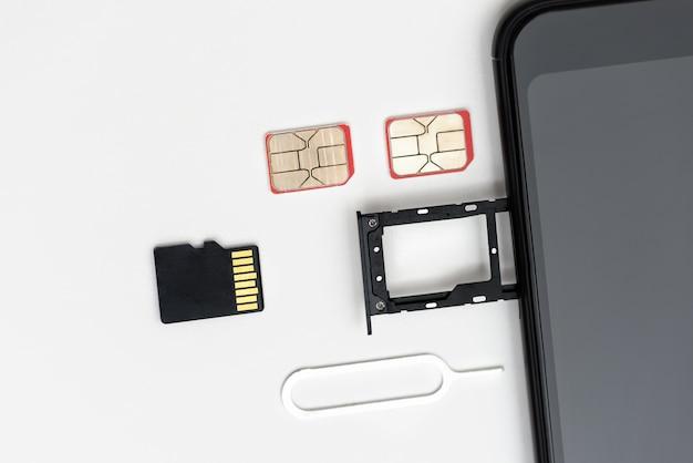 Są karty sim, karta pamięci, pin w pobliżu smartfona z otwartym gniazdem
