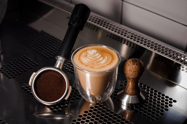Sabotaż i filiżanka kawy wypełnione dekorowanym latte na blacie