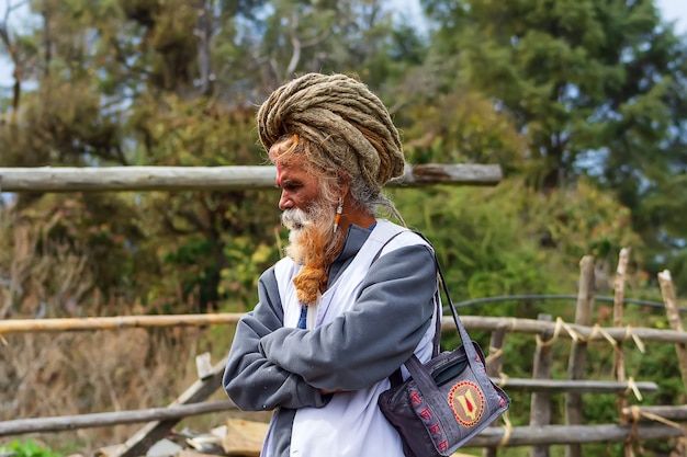 Sadhu mężczyzna z tradycyjnie pomalowaną twarzą stojący w pobliżu drewnianego ogrodzenia sadhu jest świętą osobą w hinduizmie