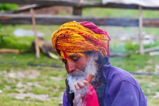Sadhu z tradycyjnie pomalowaną twarzą palący fajkę ze specjalnymi ziołami do medytacji