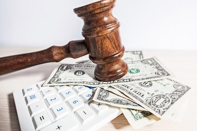 Sądzi młoteczek i pieniądze na brown drewnianym stołowym pojęciu