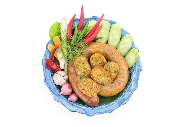 Sai aua lub pikantna kiełbasa tajska północna zawiera zioła, takie jak trawa cytrynowa, liście limonki kaffir, kolendra i inne izolowane na białym tle. widok z góry, płasko ułożony.