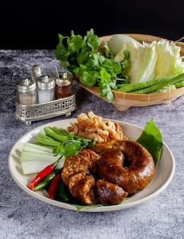 Sai aua (pikantna kiełbasa z tajlandii północnej) na drewnianej powierzchni