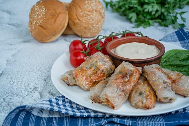 Sajgonka z mięsem i warzywami podawana na białym talerzu z sosem.