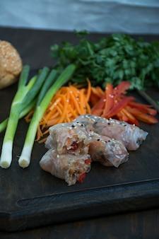 Sajgonka z mięsem i warzywami podawana na desce do krojenia.