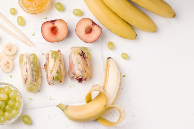 Sajgonki owocowe w papierze ryżowym obok składników z bananem, jabłkiem, winogronem i śliwką na białym tle. jest miejsce do kopiowania. danie wegetariańskie