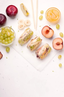Sajgonki owocowe w papierze ryżowym obok składników z bananem, jabłkiem, winogronem i śliwką na białym tle. jest miejsce na tekst