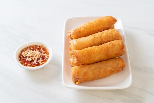 Sajgonki smażone na głębokim tłuszczu z sosem na białym talerzu