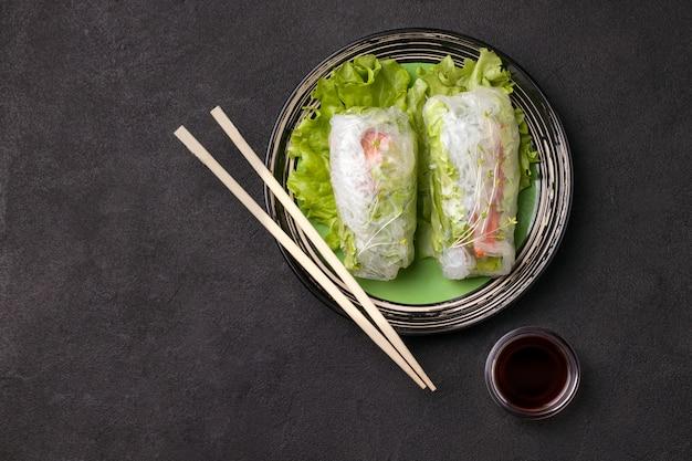 Sajgonki z pałeczkami na zielonym talerzu obok szarego sosu na czarno. jest miejsce na tekst