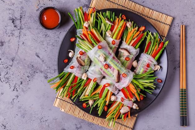 Sajgonki z warzywami i grzybami shiitake na talerzu.
