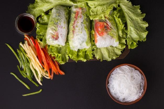 Sajgonki z warzywami na czarno. obok składników są posiekane papryki, makaron i sos sojowy. danie wegetariańskie