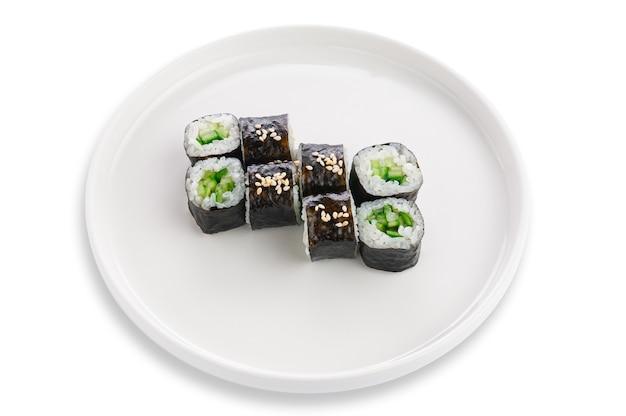 Sake maki roll z ogórkiem i sezamem. wegetariański. na białym talerzu ceramicznym. białe tło. odosobniony.