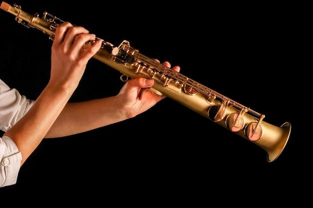 Saksofon sopranowy w rękach dziewczyny na czarnej powierzchni
