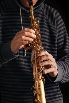 Saksofon sopranowy w rękach faceta na czarnej powierzchni